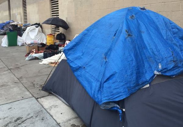 Homeless people set up tents on a sidewalk in San Diego.
