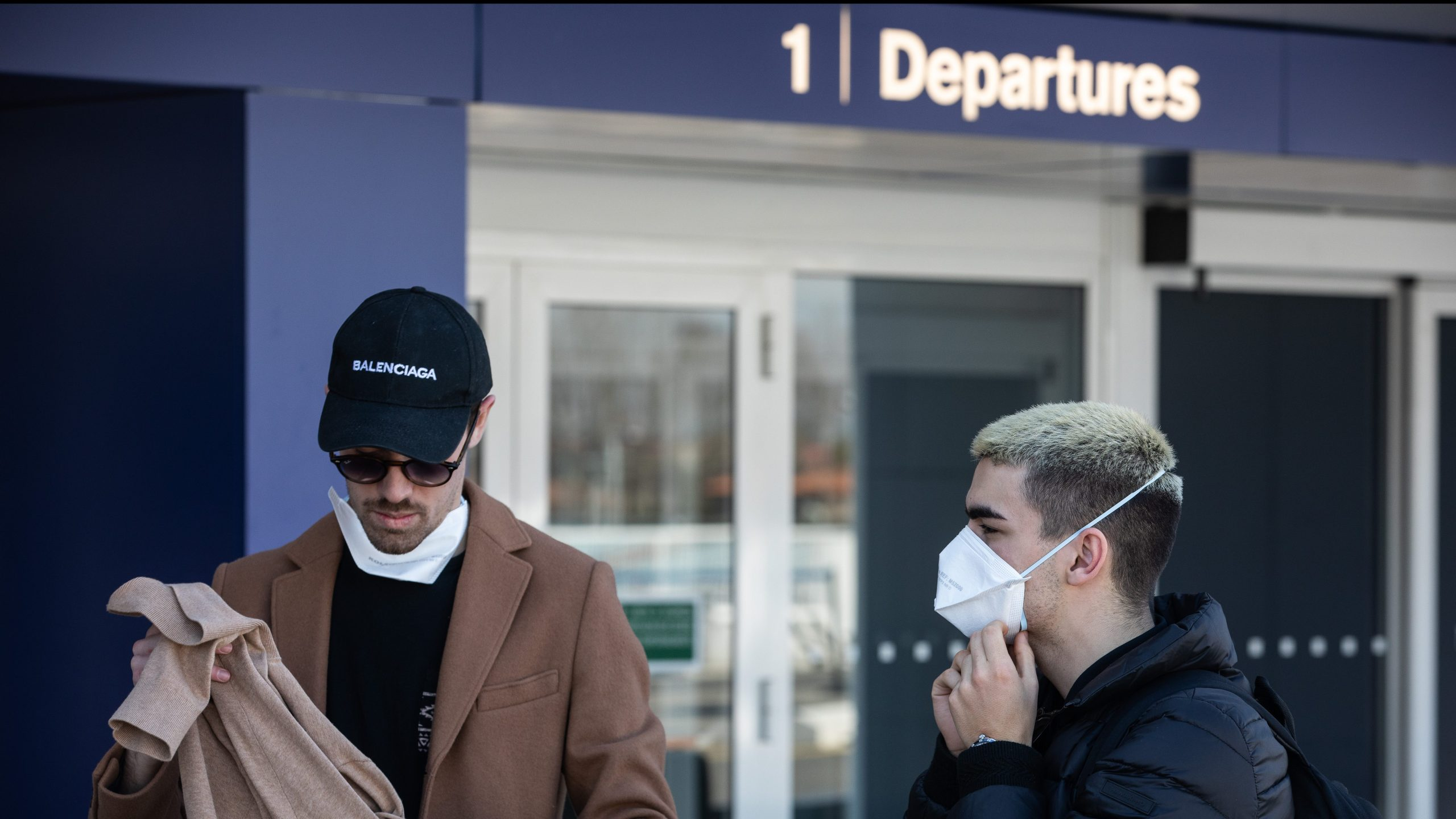 "MILAN, ITALY - MARCH 08: Two young men, wearing face masks, stand in front of the departure terminal at Linate, Milan's city airport, on March 08, 2020 in Milan, Italy. Prime Minister Giuseppe Conte announced overnight a ""national emergency"" due to the coronavirus outbreak and imposed quarantines on the Lombardy and Veneto regions, which contain roughly a quarter of the country's population. Italy has the highest number of cases and fatalities in Europe. (Photo by Emanuele Cremaschi/Getty Images)"