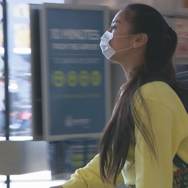 A young woman walk through San Diego International Airport wearing a face mask.