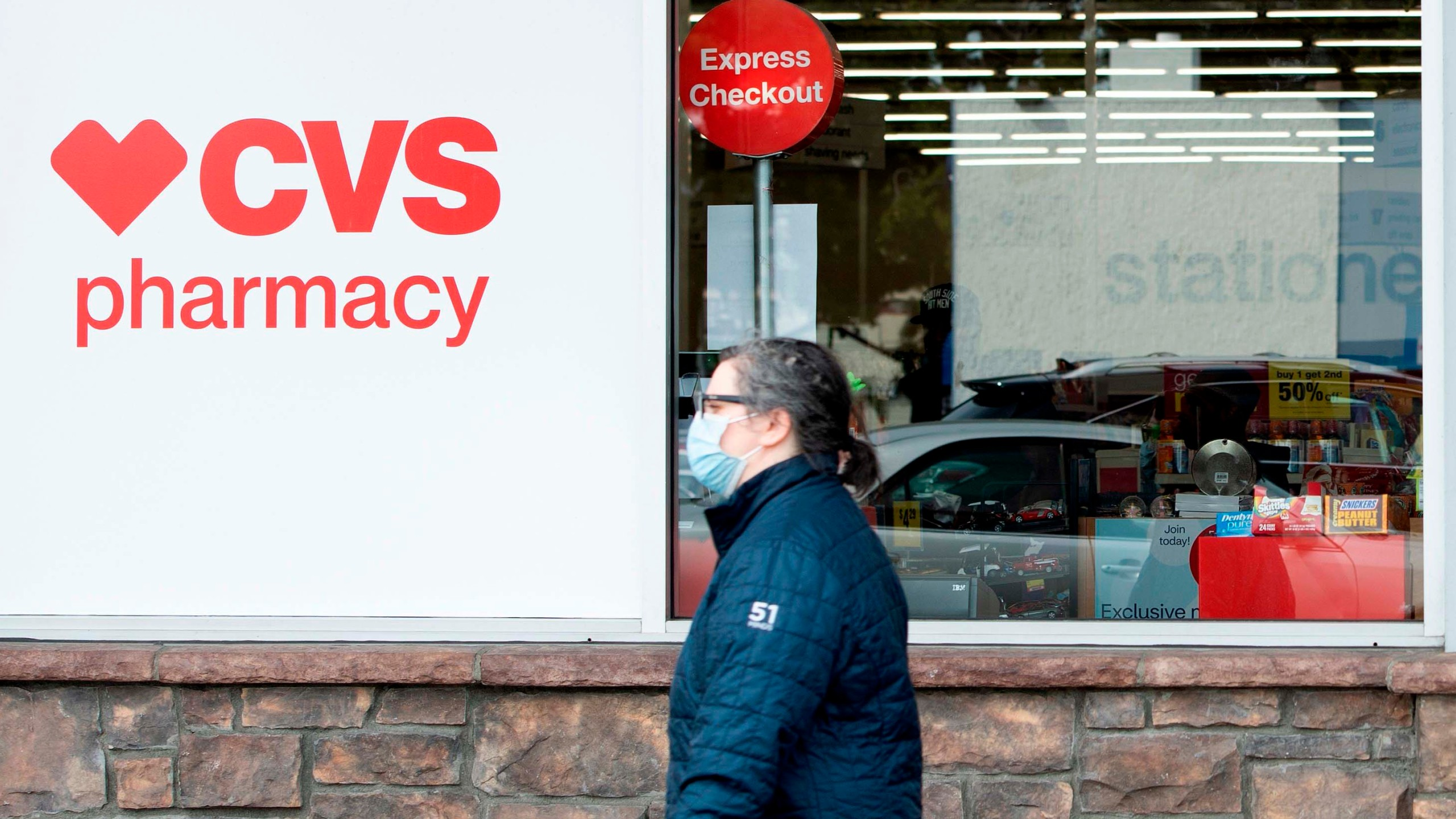 A person with a mask shops at CVS in Los Angeles during the Covid 19 crisis as California is under orders to stay home, March 31, 2020. (Photo by VALERIE MACON / AFP) (Photo by VALERIE MACON/AFP via Getty Images)