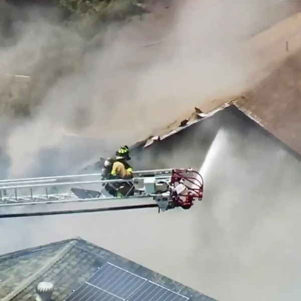 A San Diego firefighter pours water from a ladder truck onto a burning home in Mira Mesa.