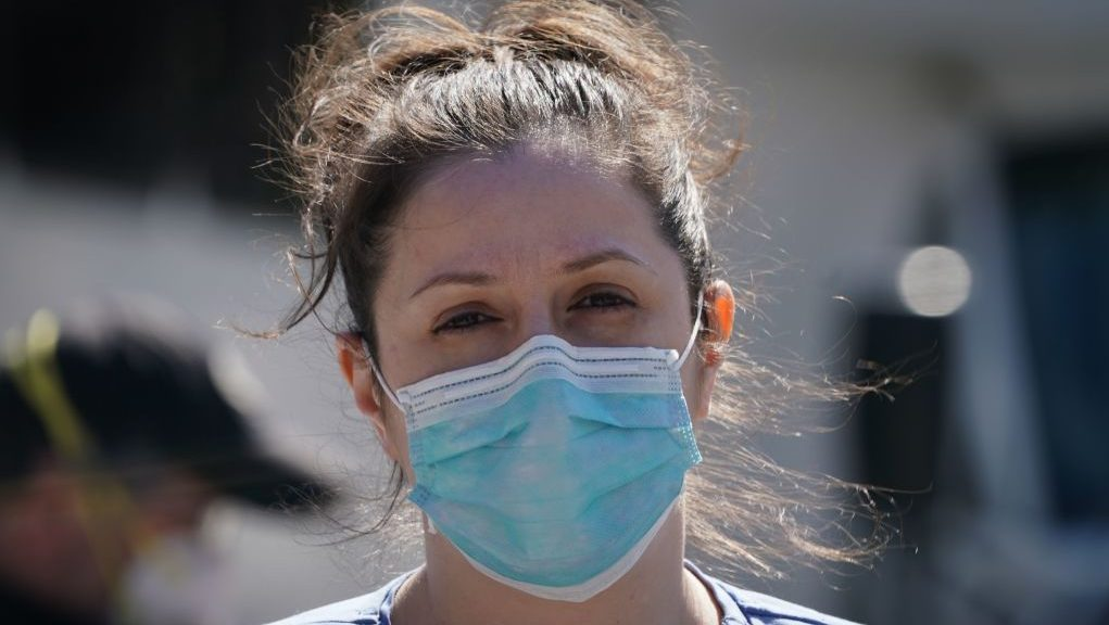 """A member of the medical staff listens as Montefiore Medical Center nurses call for N95 masks and other critical PPE to handle the coronavirus (COVID-19) pandemic on April 1, 2020 in New York. - The nurses claim """"hospital management is asking nurses to reuse disposable N95s after long shifts"""" in the Bronx. (Photo by Bryan R. Smith / AFP) (Photo by BRYAN R. SMITH/AFP via Getty Images)"""