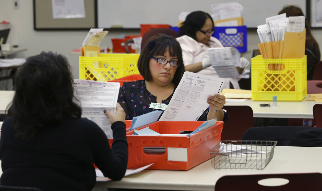 FILE - In this Wednesday, Nov. 12, 2014, file photo, Lydia Harris, a temporary worker at the Sacramento Registrar of Voters, looks over a mail-in ballot before it is sent to be counted in Sacramento, Calif. Over 100,000 mail-in ballots were rejected by election officials in California's March 2020 presidential primary, highlighting a glaring gap in the effort to ensure every vote is counted as a national dispute rages over the integrity of vote-by-mail elections. (AP Photo/Rich Pedroncelli, File)