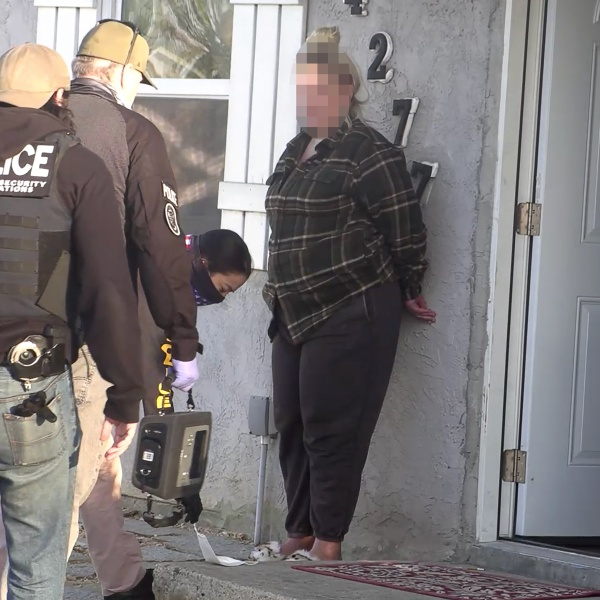 Federal drug agents detain a resident during the search of a home in the Clairemont neighborhood.